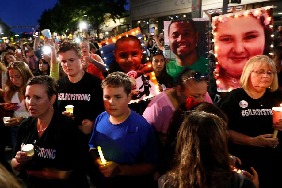 A candelight vigil on Monterey Street in Gilroy, CA, on Aug. 1, 2019, in the wake of the mass shooting at the Gilroy Garlic Festival. The photos of shooting victims, Stephen Romero, 6, Trevor Irby and Keyla Salazar, 13, are being held up. Photo: Scott Strazzante / The Chronicle
