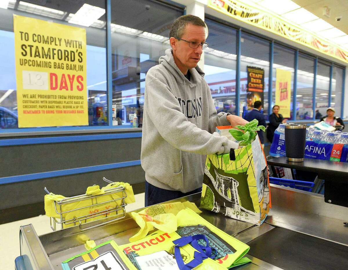 Nick D'Alessan of Stamford bags his own groceries using recyclable bags after shopping at Shop Rite in Stamford.
