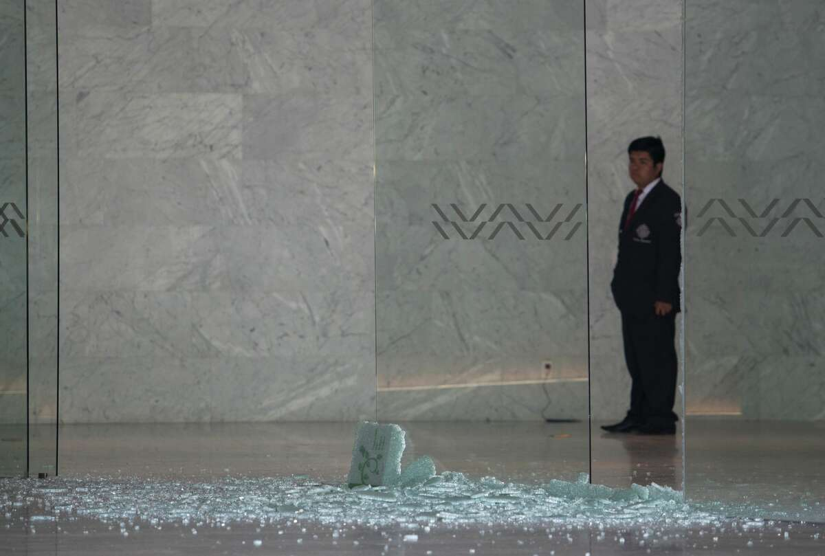 A private security guard looks at a shattered glass at a shopping mall in Mexico City on July 25, 2019 where two Israelis suspected of mafia links were shot dead on the eve. Two Israelis suspected of mafia links were shot dead in a luxury Mexico City mall in what could have been a settling of scores, Mexico's attorney general's office said on Thursday. The two men were gunned down in a restaurant inside the mall.