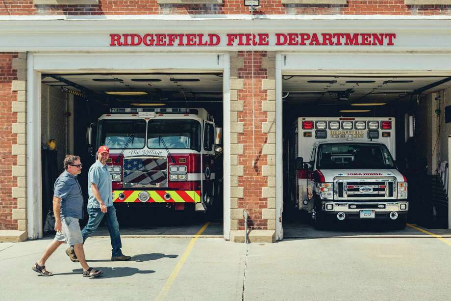 Thrown Stone Theater Company co-artistic directors from left to right Jason Peck and Jonathon Winn pass by the Ridgefield Fire Department of Ridgefield, CT. Photo: Christopher Setter / Christopher Setter/For Hearst Connecticut Media