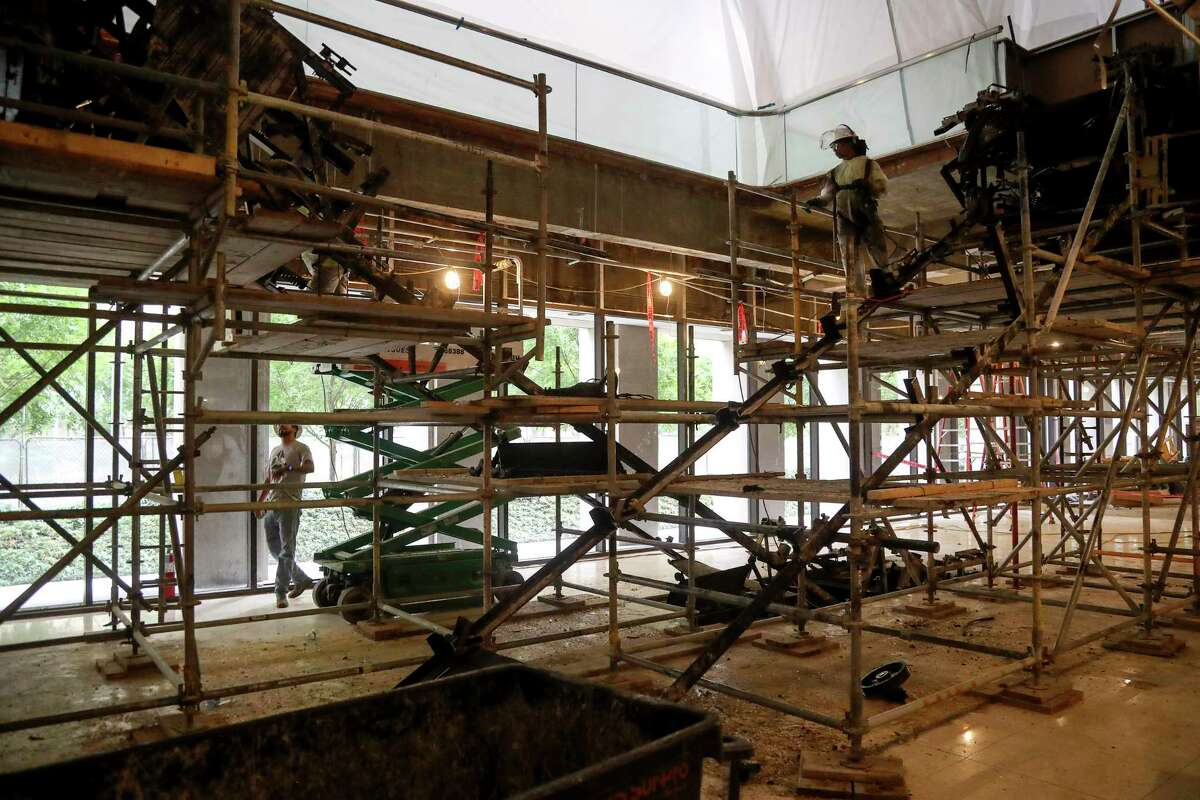 Workers remove an escalator in the lobby of Two Allen Center as part of a renovation on Tuesday, July 30, 2019, in Houston.