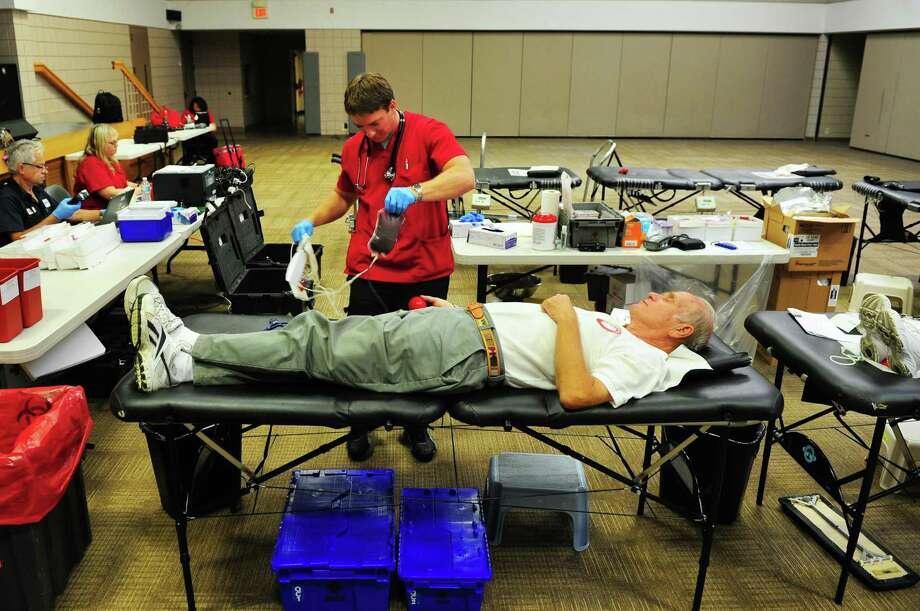 Jerry Anderson donates blood during a Red Cross blood drive held at Calvary Evangelical Free Church in Trumbull, Conn., on Wednesday Aug. 17, 2016. Working with them is phlebotomist Chris Banziruk. The summer months are among the most challenging times of years to collect enough blood and platelet donations to meet patient needs. Many regular donors delay giving while they take vacation and participate in summer activities. Photo: Christian Abraham / Hearst Connecticut Media / Connecticut Post