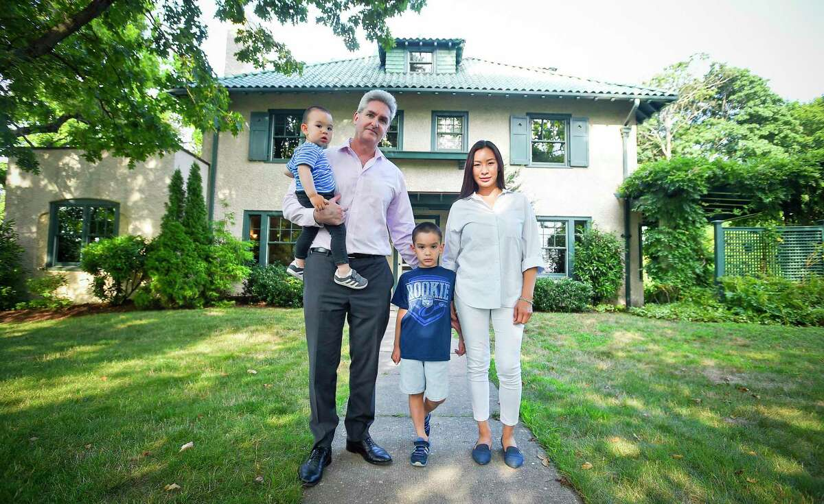 Peter Zeitsch, stands with his wife, Flora, and their sons, 5-year-old Luke and 18-month-old Mark, in front of their home in the Shippan section of Stamford, Conn., on July 30, 2019. The Zeitsches relocated from San Francisco and moved in June to the Italian villa-style house, which stands on Shippan Avenue. The home's approximately $1 million sale to the Zeitsches was brokered by Halstead Real Estate.