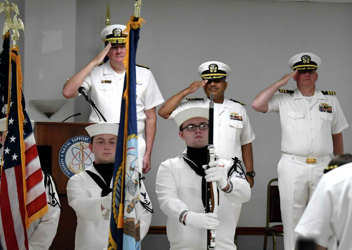 Rear Adm. Charles Rock, left, Cmdr. Christopher Tejeda, center, and Cmdr. Phillip Boyce, right, salute the colors during a change of command ceremony for the Naval Support Activity Saratoga Springs facility on Friday, Aug. 2, 2019, at the Knights of Columbus Hall in Saratoga Springs, N.Y. Cmdr. Boyce replaced Cmdr. Tejeda as base commander. (Will Waldron/Times Union)