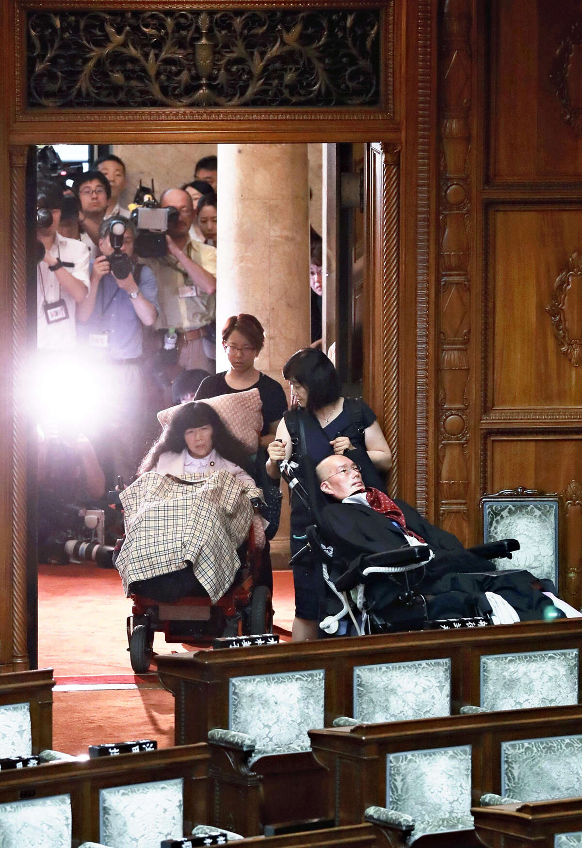 Sitting in wheelchairs, newly elected House of Councillors lawmakers Eiko Kimura, left, and Yasuhiko Funago enter the Diet chamber Thursday.