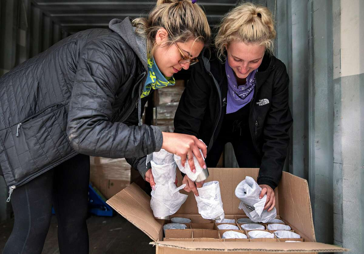Cassey Ramirez (left) and Sydney Kerns work to unbox a shipment of reusable cups for Outside Lands Music Festival guests during set up for the Outside Lands Music Festival at the Golden Gate Park Polo Field in San Francisco, Calif. Thursday, August 1, 2019.