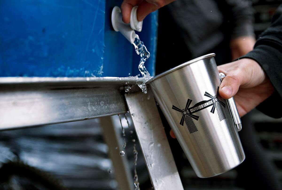Sydney Kerns pours water into a reusable cups created for Outside Lands Music Festival guests during set up for the Outside Lands Music Festival at the Golden Gate Park Polo Field in San Francisco, Calif. Thursday, August 1, 2019.