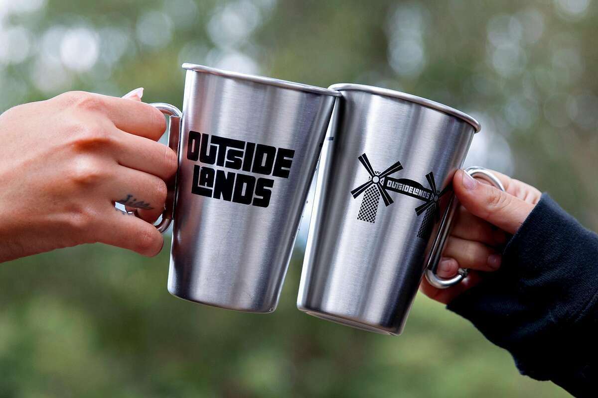 Cassey Ramirez (left) and Sydney Kerns pose with two reusable cups created for Outside Lands Music Festival guests during set up for the Outside Lands Music Festival at the Golden Gate Park Polo Field in San Francisco, Calif. Thursday, August 1, 2019.