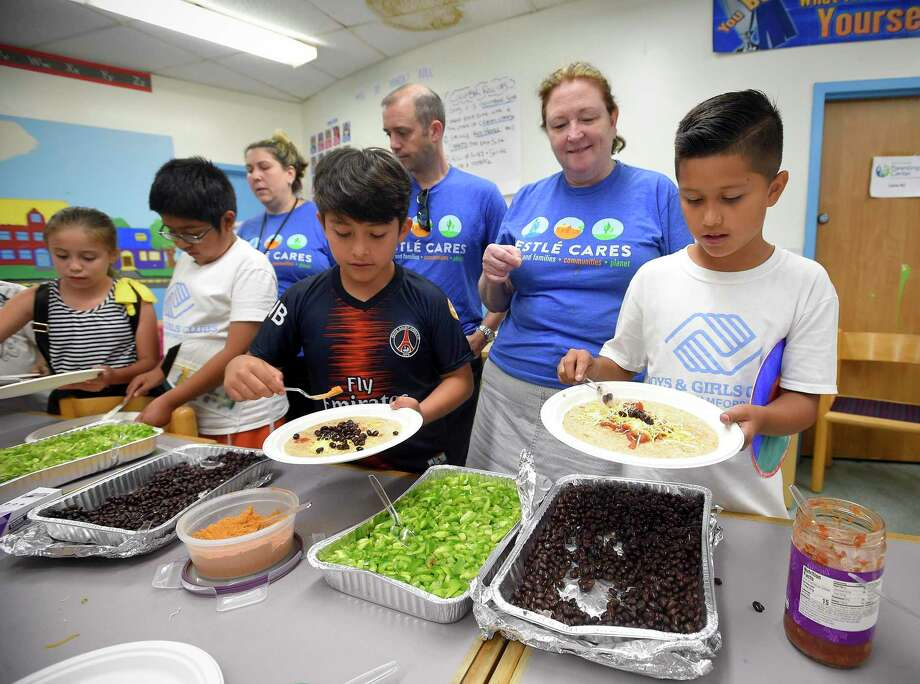 As part of its fourth annual Nestlé Cares day of service, over 100 Nestlé employees based in Stamford, including Maureen Deacy, at center in photo above, worked with local children on Thursday to prepare healthy snacks and share valuable nutrition and hydration information. At right, Deacy, works with Kristel Pimentec, while Yasmine Bastien enjoys a cucumber roll. The annual day of service is part of the company's larger efforts to create a healthier future for its consumers and associates. Combating hunger through community partnerships is part of Nestlé's over 150-year commitment to enhance nutrition and provide healthy foods and beverages. Nestlé seeks to help 50 million children worldwide live healthier lives by 2030 as part of its global Nestlé for Healthier Kids initiative. Photo: Matthew Brown / Hearst Connecticut Media / Stamford Advocate