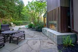 An outdoor fireplace warms a stone patio behind the gated home in Mill Valley.