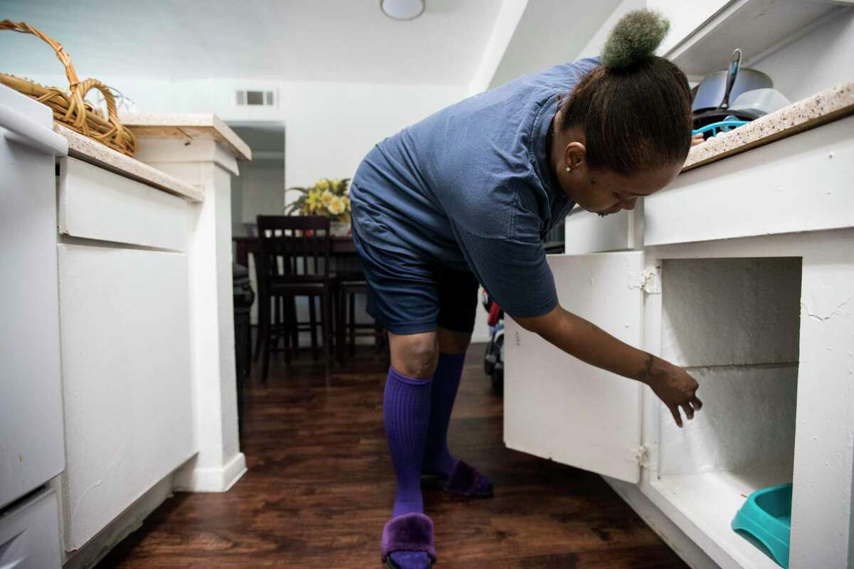 Tunisia Coachman shows the cabinet under her sink that she says is falling apart in the flood-damaged Arbor Court apartments on Wednesday, July 24, 2019, in Houston.