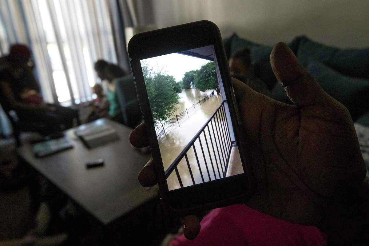Chelsea Williams looks a video of flooding in the Arbor Court apartments.