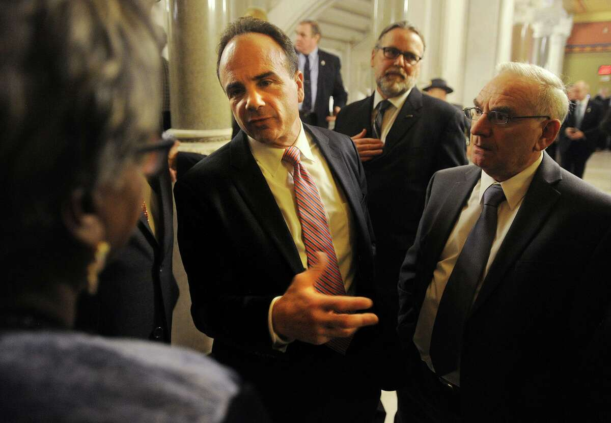 Bridgeport Mayor Joe Ganim talks with Sen. Marilyn Moore, left, outside the House of Representatives where he attended Gov. Dannel P. Malloy's budget address at the Capitol in Hartford, Conn. on Wednesday, February 3, 2016. Attending with Ganim was Bridgeport Democratic Town Committee Chair Mario Testa, right.