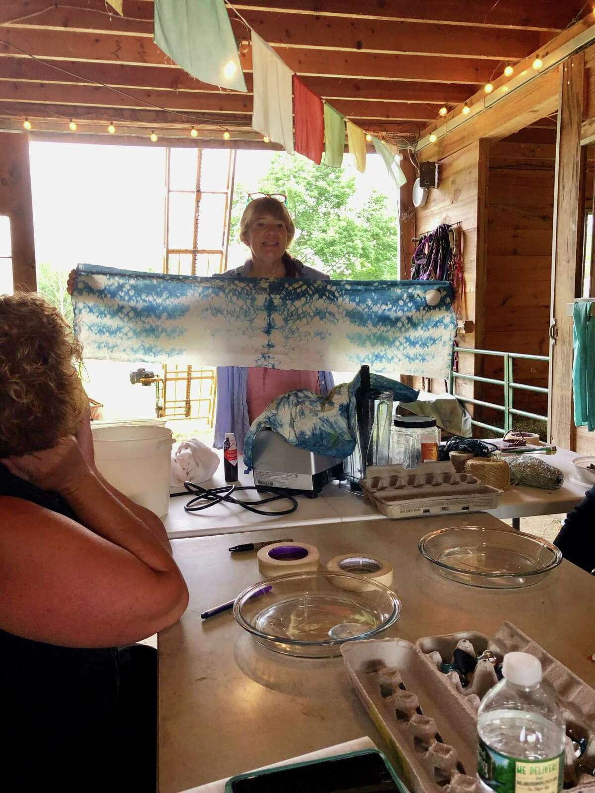 Wing & A Prayer owner Tammy White shows an example of previously dyed fabric to the workshop group. (Photo by Cecily Bailey)