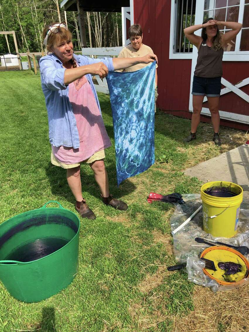 Farm owner Tammy White shows a newly dyed fabric, pulled from the five-gallon vat, that is ready to be rinsed. (Photo by Cecily Bailey)