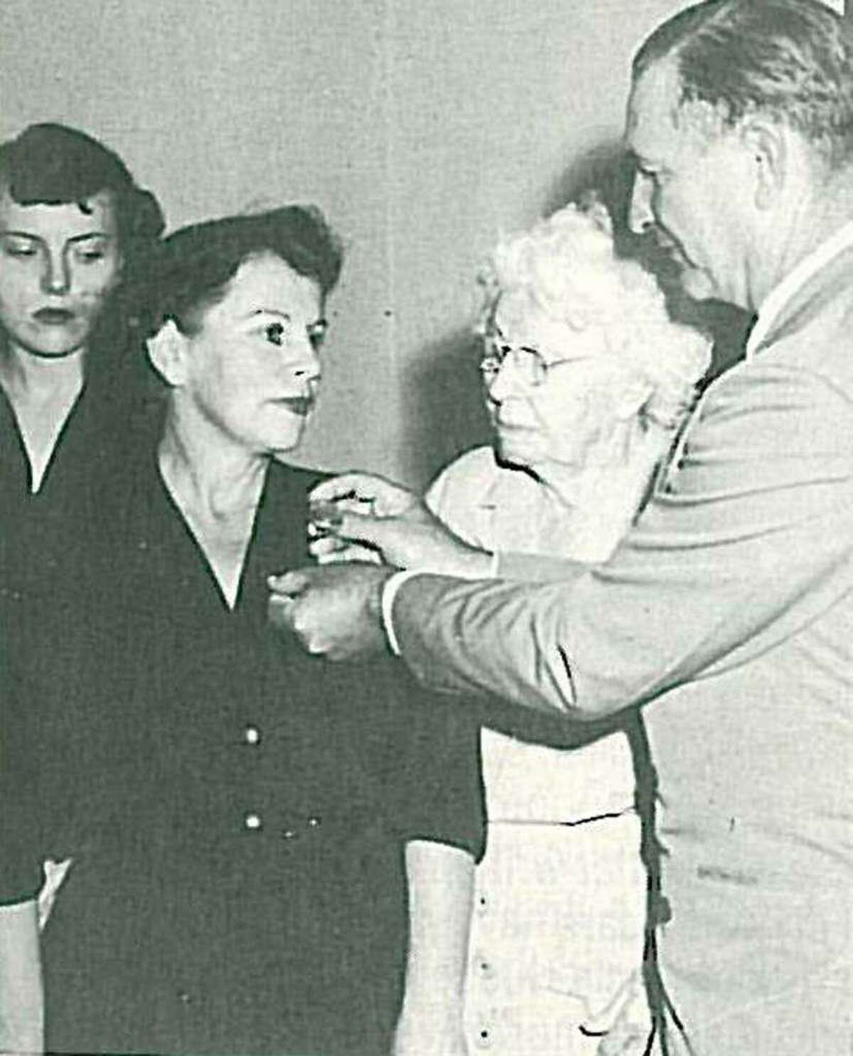Three generations of the Cochran family as Fannie Pearl Surratt has her Montgomery County Sheriff's badge pinned on by her parents. Pictured from left are Gloria Surratt Burch, Fannie Pearl Surratt and Laura G. Cochran and Fred Cochran.