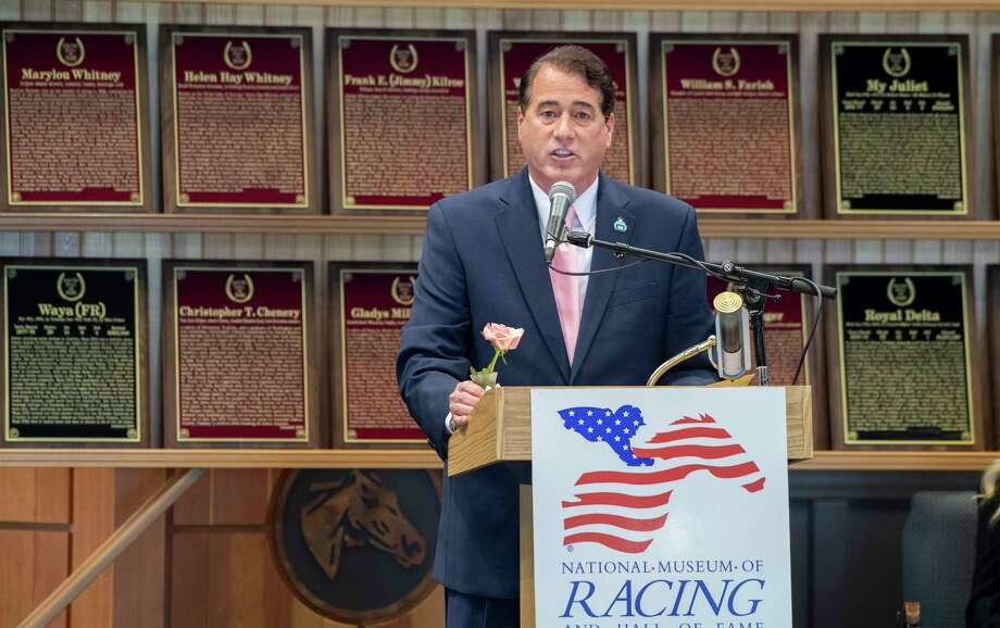 John Hendrickson, holding a Whitney Rose which he had commissioned for his late wife, accepts the Pillars of the Turf award for Marylou Whitney at the National Museum of Racing and Hall of Fame Inductions held at the Fasig Tipton sales arena Friday Aug. 2, 2019 in Saratoga Springs, N.Y.  Photo Special to the Times Union by Skip Dickstein