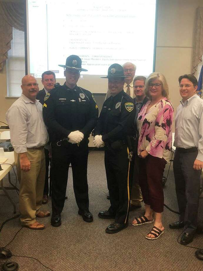 Officer Anthony Armeno, left, was promoted to corporal and Officer Robert Burke, right, will be the new Heritage Village Community Resource Officer. Both are pictured with the Board of Selectmen at the Aug. 1 Board of Selectmen meeting in Southbury, Conn. Photo: Southbury Police Department's Facebook Page