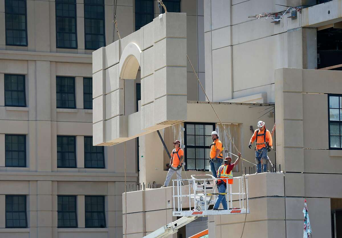 Workers move a prefabricated section into place during construction of the huge Escondido Village Graduate Residences development in Stanford, Calif. on Thursday, Aug. 1, 2019. When completed in time for the Fall 2020 school session, the four 10-story buildings will house more than 2,400 Stanford University graduate students.
