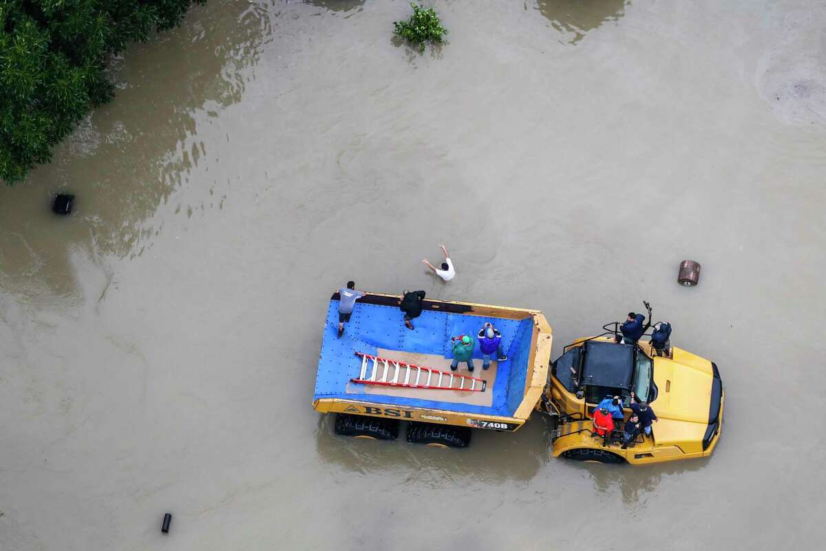 Flood victims are evacuated on a large truck in a neighborhood flooded by Tropical Storm Harvey on Aug. 29, 2017, in Houston.