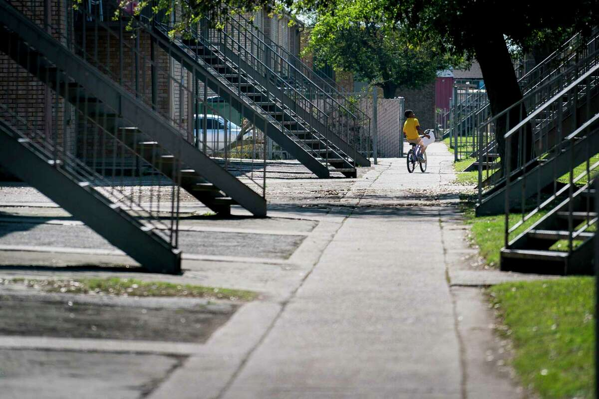 A boy rides his bicycle through the Sandpiper Cove apartments in Galveston, which are privately owned but subsidized by the U.S. Department of Housing and Urban Development.