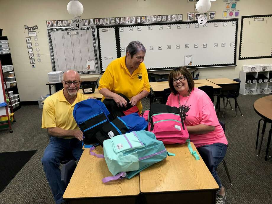Panorama Lions members Bill Stephens (left) and Sandra Whiteker review a sampling of the 250 backpacks that are being donated to students in the Willis Independent School District with Michelle Witham, counselor at Hardy Elementary. Photo: Photo Courtesy Panorama Lions Club