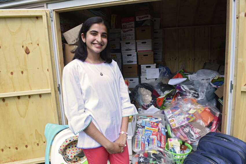 Alvira Tyagi, 16, stands by the shed of donations she and volunteers collected for refugees at the Colonie Town Library on Friday, Aug. 2, 2019 in Colonie, N.Y. Tyagi started a club called Teens for Refugees at Shaker High School. She will be donating the supplies to local refugee support organizations RISSE and USCRI. (Lori Van Buren/Times Union)