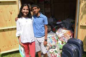 Alvira Tyagi, 16, and her brother Aarya, 13, stand by the shed of donations they and volunteers collected for refugees at the Colonie Town Library on Friday, Aug. 2, 2019 in Colonie, N.Y. Tyagi started a club called Teens for Refugees at Shaker High School. She will be donating the supplies to local refugee support organizations RISSE and USCRI. (Lori Van Buren/Times Union)