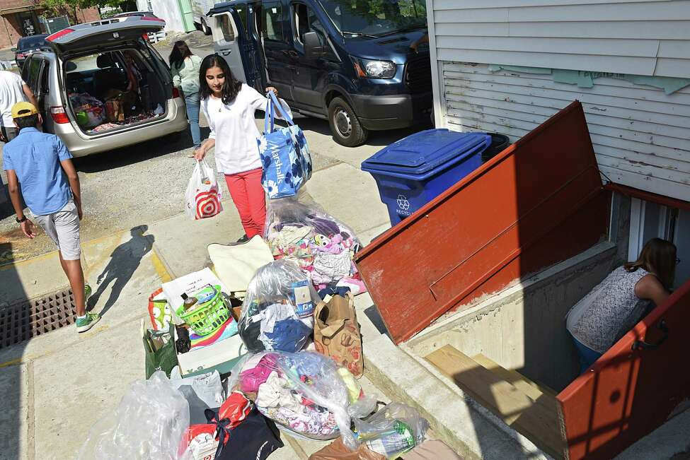 Alvira Tyagi, 16, center, unloads a van of donations at RISSE that she and volunteers collected for refugees at the Colonie Town Library on Friday, Aug. 2, 2019 in Albany, N.Y. Tyagi started a club called Teens for Refugees at Shaker High School. She will be donating the supplies to local refugee support organizations RISSE and USCRI. Alvira's family helps her unload as RISSE volunteer coordinator Theresa Alexander brings down the donations to the donation room at right. (Lori Van Buren/Times Union)