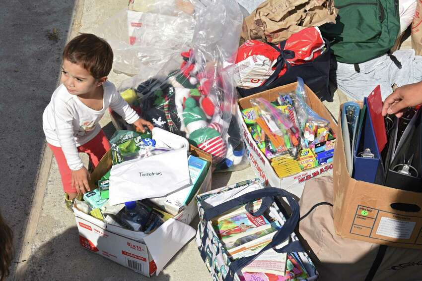 Mustava Hambard, 18 mos. checks out donations brought to RISSE by Alvira Tyagi that she and volunteers collected for refugees at the Colonie Town Library on Friday, Aug. 2, 2019 in Albany, N.Y. Tyagi started a club called Teens for Refugees at Shaker High School. She will be donating the supplies to local refugee support organizations RISSE and USCRI. (Lori Van Buren/Times Union)