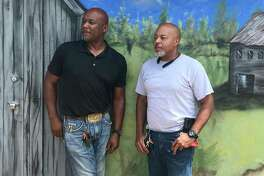 """Cousins Victor Morrison and Anthony """"Dondo"""" Upshaw, standing before a mural created at Uncle Doug's by another cousin, are hoping to attract customers from beyond Lufkin and Nacodoches."""