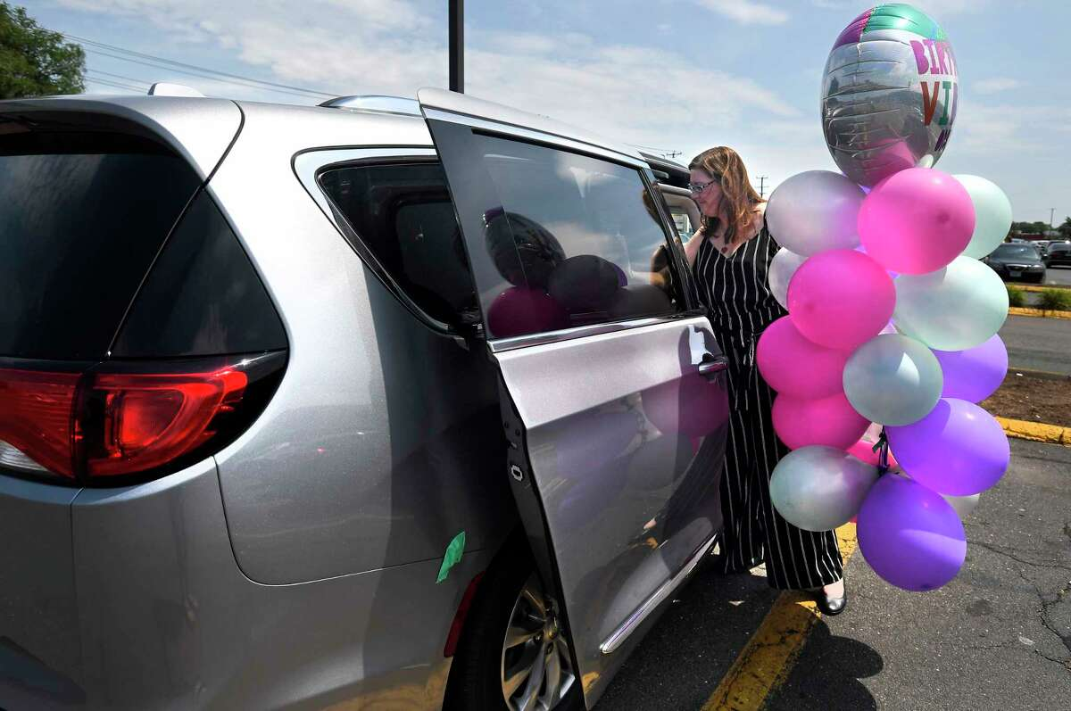 In this Tuesday, July 16, 2019, Melanie Matcheson loads balloons into her Chrysler Pacifica in Southington, Conn. For Melanie Matcheson, no vehicle other than a minivan could efficiently haul her family of two adults and five children ages 2 to 22. (AP Photo/Jessica Hill)