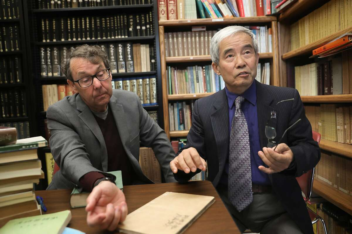 """Director of SF State's Chinese flagship program Charles Egan (left) looks at an ancient chinese history annotation with associate VP for International Education Dr. Yenbo Wu (right) in the Chinese Reading Room in the humanities building at San Francisco State University on Thursday, Aug. 1, 2019 in San Francisco, Calif. Dr. Yenbo Wu was director of the """"Confucius Institute"""" on campus for 14 years which was partially funded by the Chinese government to promote language instruction and Chinese culture."""