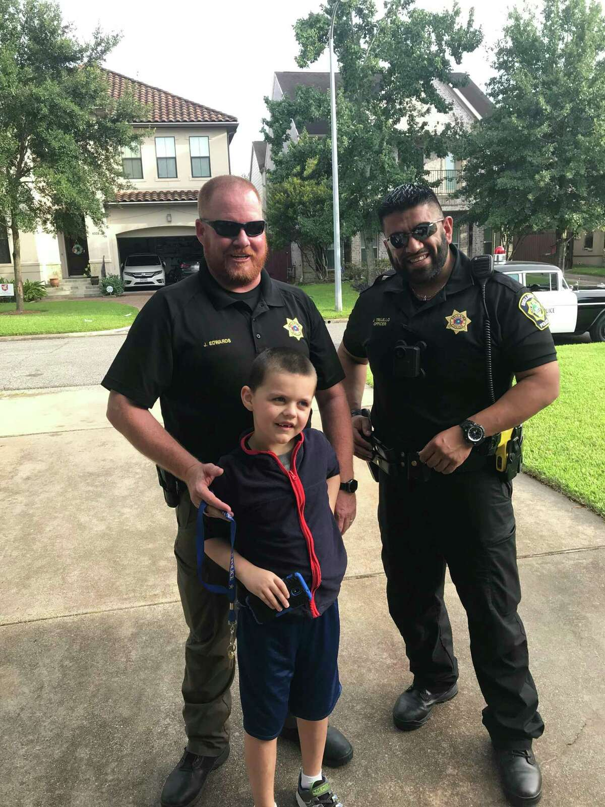 Officer Edwards and Officer Trujillo pose for a photo with Jack when the officers came to the Selig's house to enroll Jack into the Home Safe Bellaire Program. Bellaire resident Liz Selig helped the Bellaire Police Department implement the Home Safe Bellaire Program after her non-verbal son Jack wandered away from home.