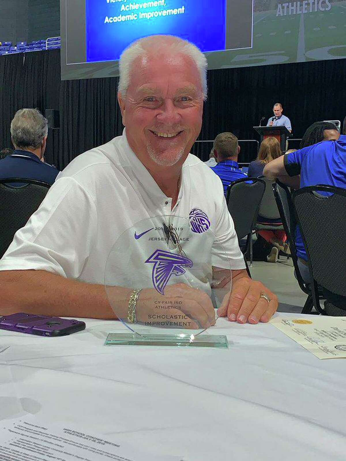 Jersey Village athletic coordinator/head football coach David Snokhous is all smiles after the Falcons won the Academic Improvement Award at the Cypress-Fairbanks ISD Athletic Department Annual HS Coaches training, July 29, at the Berry Center.