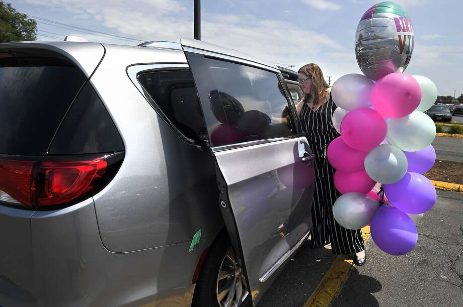 Above: Melanie Matcheson loads balloons into her Chrysler Pacifica in Southington, Conn. Below: Sisters Caroline (left) and Keiley play and older sister Georgianna looks out a window as Matcheson drives. Photo: Photos By Jessica Hill / Associated Press