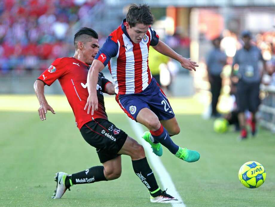Chives Carlos Fierro, right, tries to get past Atlas's Jose Antonio Madonna from Liga MX soccer exhibition match between Chivas and Club Atlas on Wednesday, July 5, 2017 Photo: Ron Cortes / For The San Antonio Express-News / Freelance
