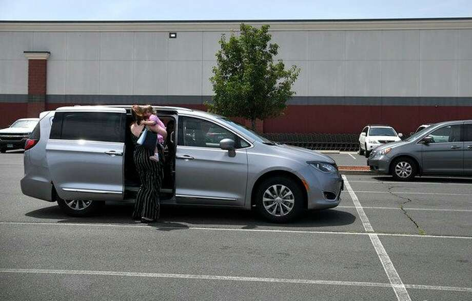 In this Tuesday, July 16, 2019, Melanie Matcheson picks up daughter Caroline out the car seat inside her Chrysler Pacifica in a shopping area parking lot in Southington, Conn. Melanie bought an eight-passenger silver Pacifica in mid-June for about $31,000, getting an $8,000 discount. (AP Photo/Jessica Hill) / Copyright 2019 The Associated Press. All rights reserved