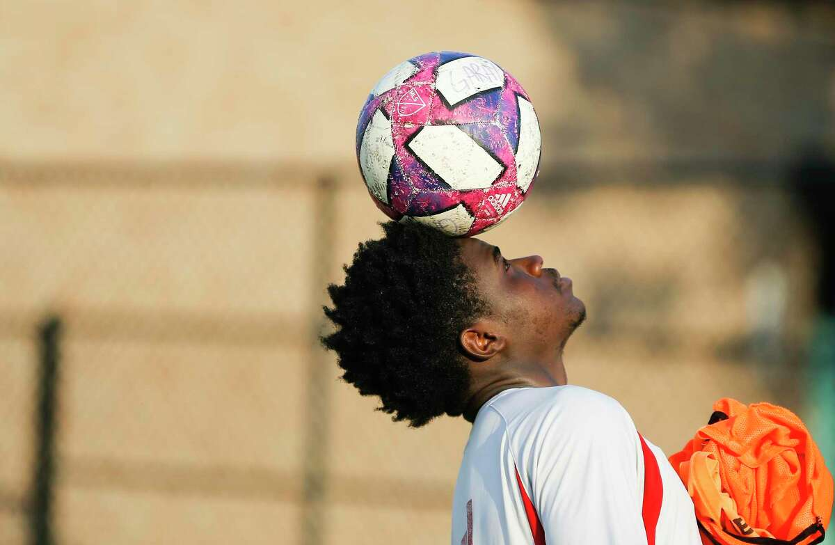Samuel Nseng balances a ball on his head after practice with reVision FC on Thursday, Aug. 1, 2019 in Houston. The Houston Dynamo has teamed up with two organizations to help set up youth soccer programs for refugees.