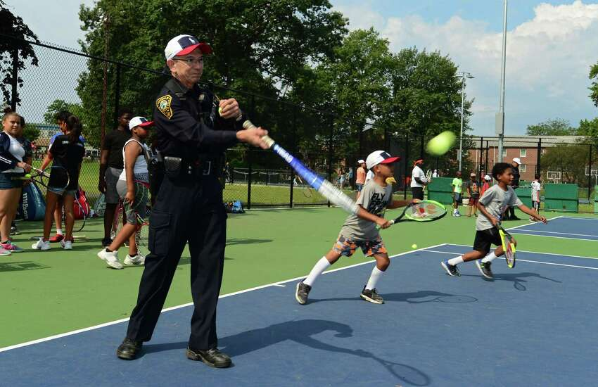 Members of the Community Police Services Division took to the tennis courts with campers from Norwalk Grassroots Tennis & Education Friday, August 2, 2019, at the tennis courts at Nathaniel Ely School in Norwalk, Conn. The annual visits to the program are an effort to form positive relationships with Norwalk's underserved youth. Norwalk PAL, a nonprofit that provides cultural, educational and athletic experiences to local children, has consistently donated money to the program. Each year, officers join the children for a friendly volley on the Nathaniel Ely School tennis courts.