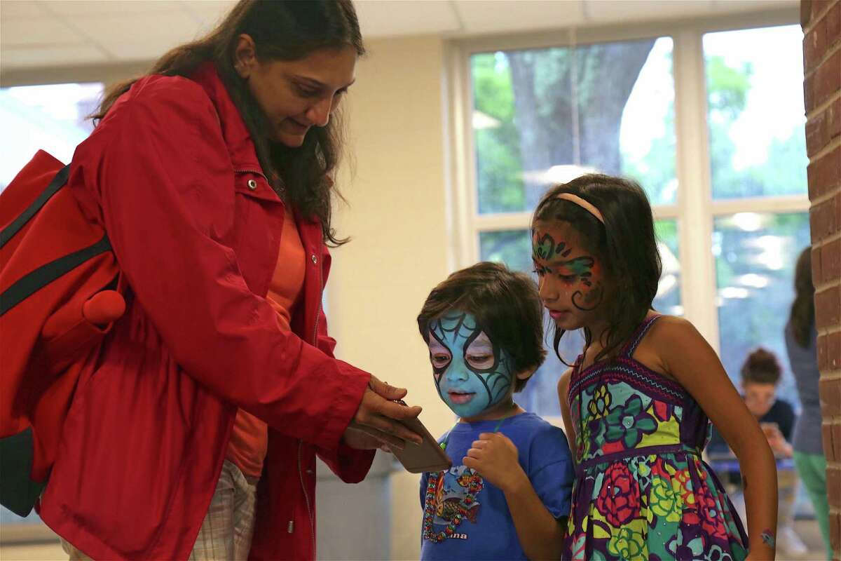 Sapna Iyer of Southport shows her kids, Dhruv, 4, and Moksha, 5, a picture of their faces at the Secret Agent 23 Skidoo performance held at Saugatuck Elementary School on Wednesday, July 31, 2019, in Westport, Conn.