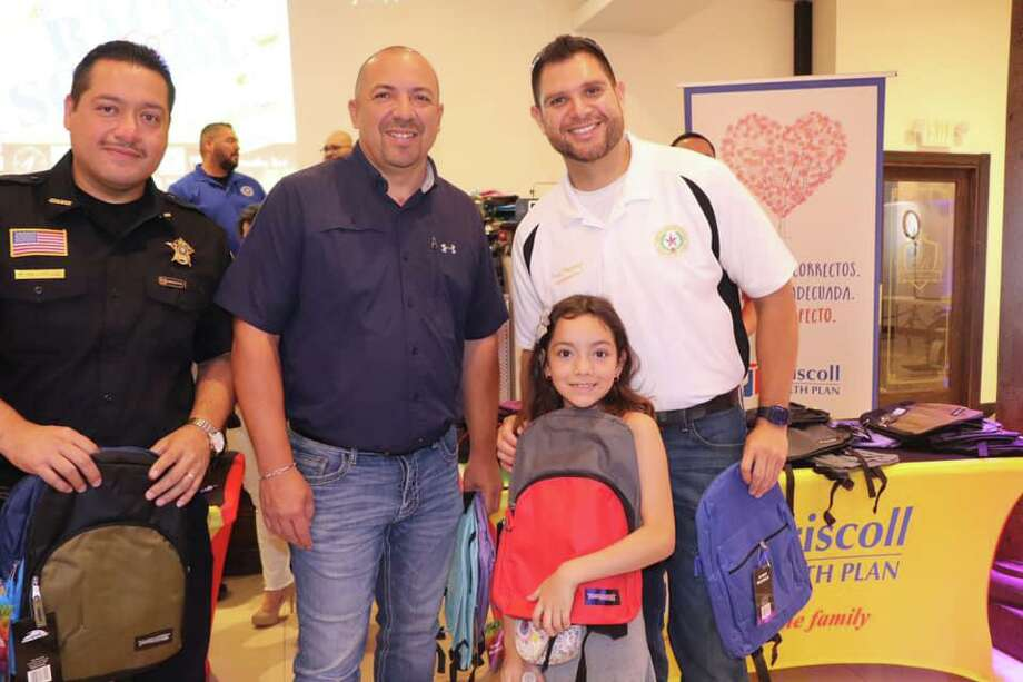 Precinct 2 Constable Mike Villarreal, Precinct 2 Place 1 Justice of the Peace Bobby Quintana and Precinct 1 Commissioner Jesse Gonzalez handed out more than 1,000 backpacks during the Fourth Annual Back to School Backpack and Supplies Giveaway. Photo: Courtesy Photo /Precinct 1 Commissioner's Office