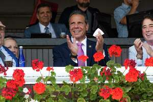 Governor Andrew Cuomo, left shares a winning moment with a winning $20 win ticket with John Hendrickison, the husband of the late socialite Marylou Whitney, right and NYRA Board Chairman Michale J. DelGuidice during a brief visit to the Saratoga Race Course Saturday, Aug. 3, 2019 in Saratoga Springs, N.Y.  Photo Special to the Times Union by Skip Dickstein