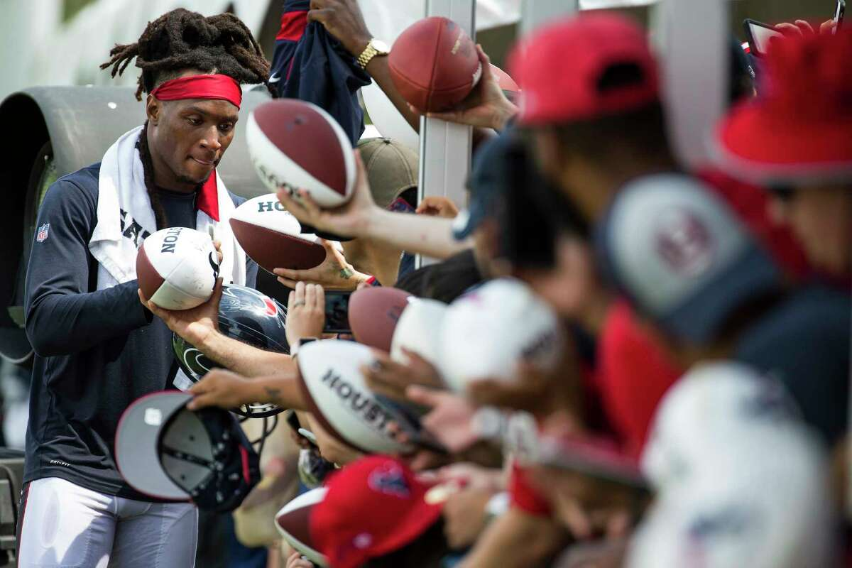 Houston Texans wide receiver DeAndre Hopkins, left, signs autographs during training camp at the Methodist Training Center on Saturday, Aug. 3, 2019, in Houston.