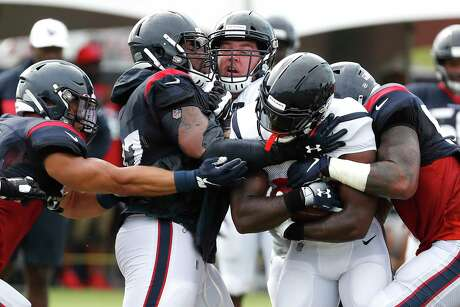 Houston Texans running back Lamar Miller gets caught by defensive end Angelo Blackson (97) as he runs the ball through the line during training camp at the Methodist Training Center on Saturday, Aug. 3, 2019, in Houston.
