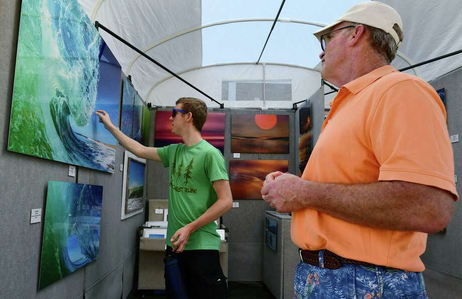 At left, Jim Cox and his son Cody Cox look at the work of photography David Siecziewicz during The SoNo Arts Festival on Saturday in South Norwalk. At right, Glorianna Restrepo and Phillippe Lerebours look at items from Silver lining during The SoNo Arts Festival. The festival which continues Sunday offers over 125 juried fine art and craft artists, a Children's Art Playground, performing artists, multiple music stages and a Puppet Parade, which winds its way through the streets. Photo: Erik Trautmann / Hearst Connecticut Media / Norwalk Hour