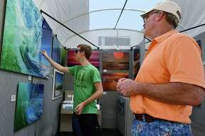 At left, Jim Cox and his son Cody Cox look at the work of photography David Siecziewicz during The SoNo Arts Festival on Saturday in South Norwalk. At right, Glorianna Restrepo and Phillippe Lerebours look at items from Silver lining during The SoNo Arts Festival. The festival which continues Sunday offers over 125 juried fine art and craft artists, a Children's Art Playground, performing artists, multiple music stages and a Puppet Parade, which winds its way through the streets.