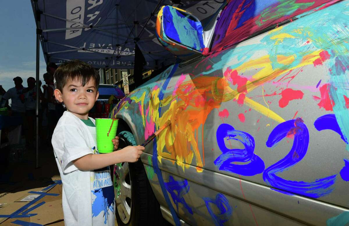 Thomas Mullarkey, 2, of Norwalk paints a car for sponsor Garavel Suburu during The SoNo Arts Festival Saturday, August 3, 3019, in South Norwalk, Conn. The festival which continues Sunday offers over 125 juried fine art and craft artists, a Children's Art Playground, performing artists, multiple music stages, and a Puppet Parade which winds its way through the streets.