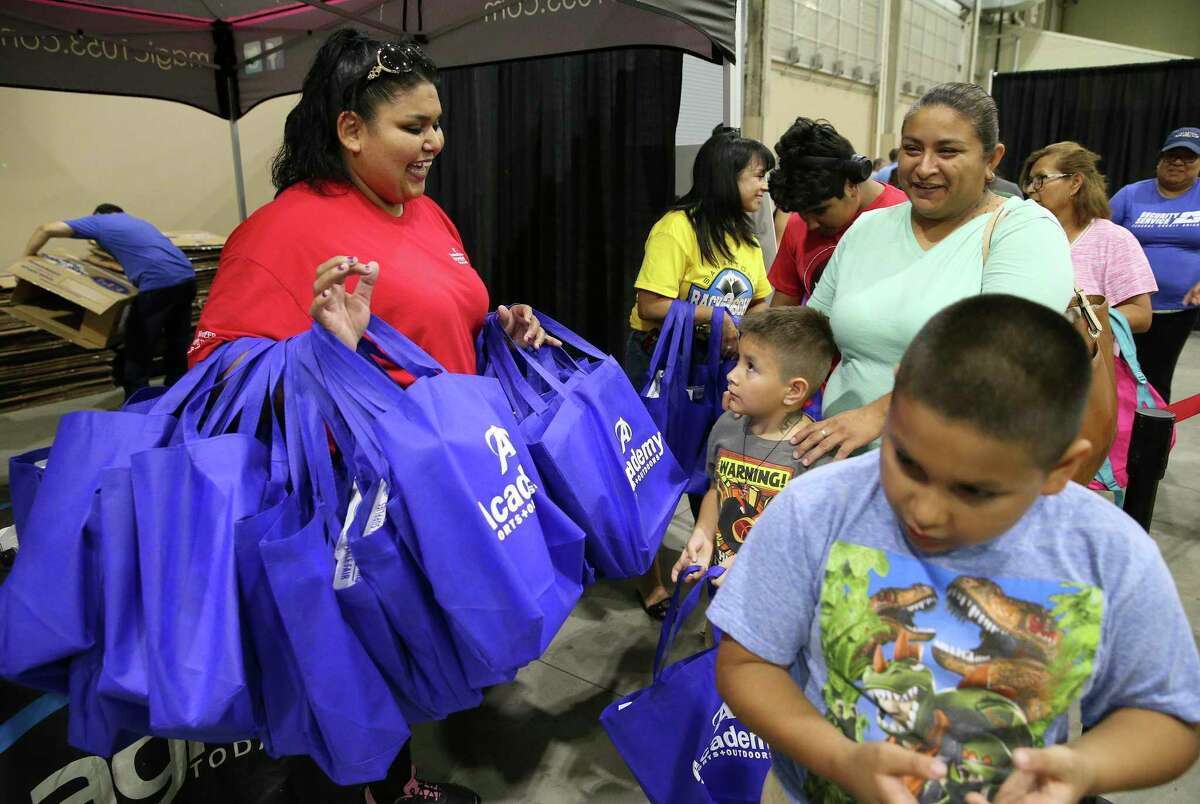 Volunteer Ilda Cano (left) from IBC Bank carries armfuls of school supplies to hand out as a large attendance of parents with their children fill the Expo Hall at Freeman Coliseum for the annual back-to-school event on Saturday, Aug. 3, 2019.