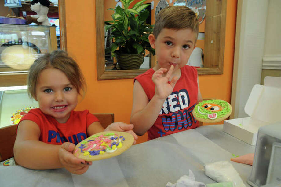 Four-year-old Reagan and six-year-old Maddux Johnson of Bethalto show their creations at Cookie Factory Bakery & Cafe in Alton Square Mall. Photo: David Blanchette | For The Telegraph